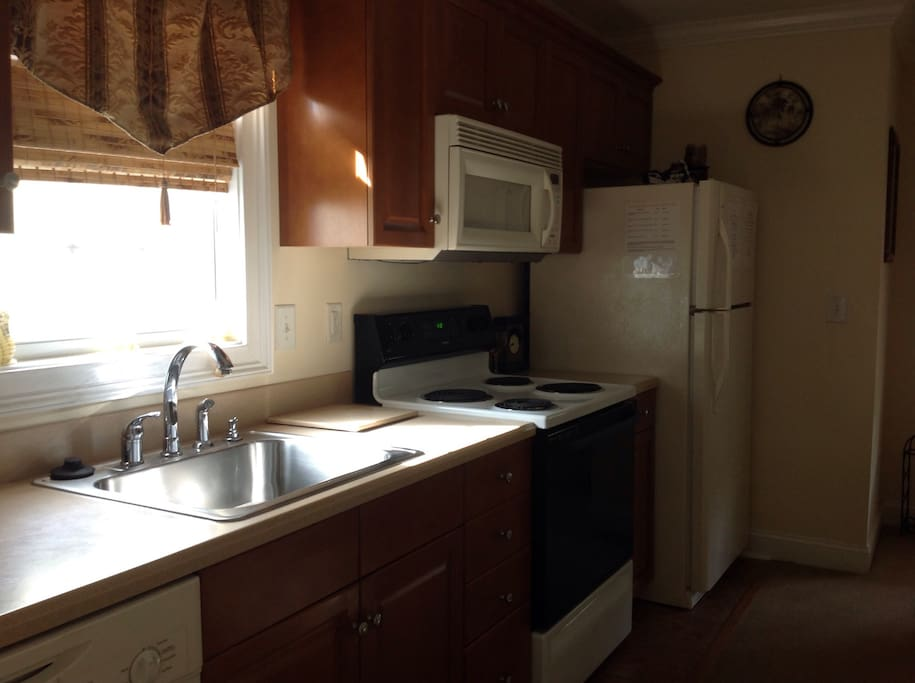 Kitchen features a full sized refrigerator, dishwasher, range, microwave & garbage disposal. Dishes and traditional kitchen items are there for you use.