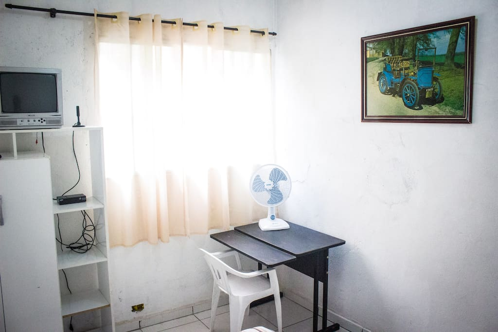 Imagem complementar do quarto com vista para TV, ventilador e escrivaninha