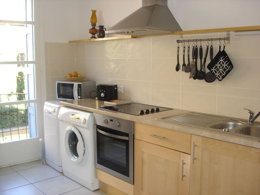 One side of kitchen. Lots of cupboards and table for two.