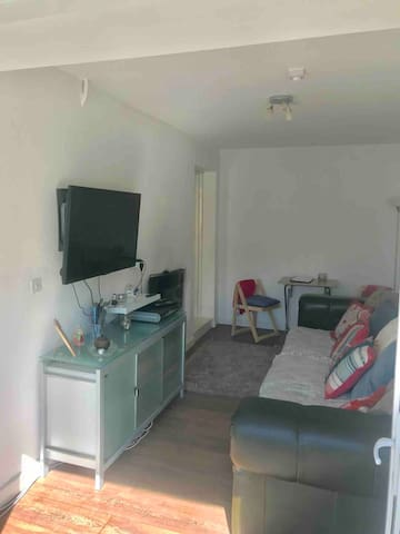Large living room with sofa, sky TV, patio doors to the car park, WiFi and an electric fireplace