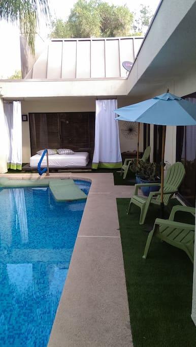 Lounging adirondaks & queen-sized mattress along private backyard pool...