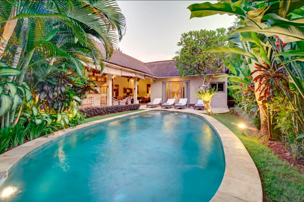 The wide private pool of the villa, surrounded by a luxurious tropical garden