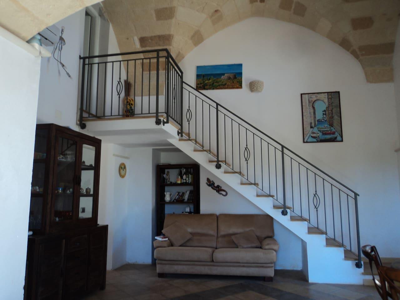 La sala con la scala che accede alla camera da letto nel soppalco