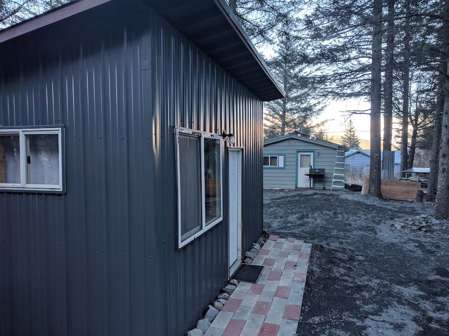 1st Avenue view of Spruce Camp Cabin with tiny house in background. Bathroom & kitchen available in tiny house.
