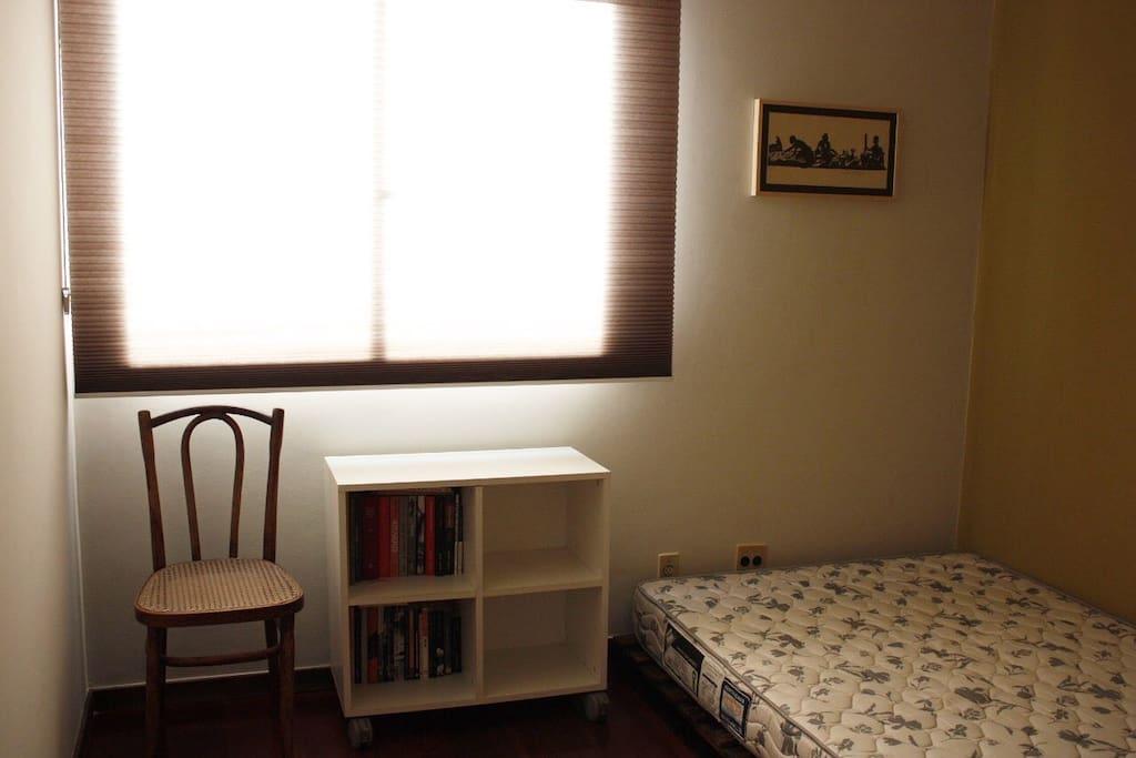 quarto com colchão de casal em cama de pallet, ventilador, blackout e cortina plissada. neste quarto, é possível acomodar uma 3a pessoa em colchão de solteiro no chão
