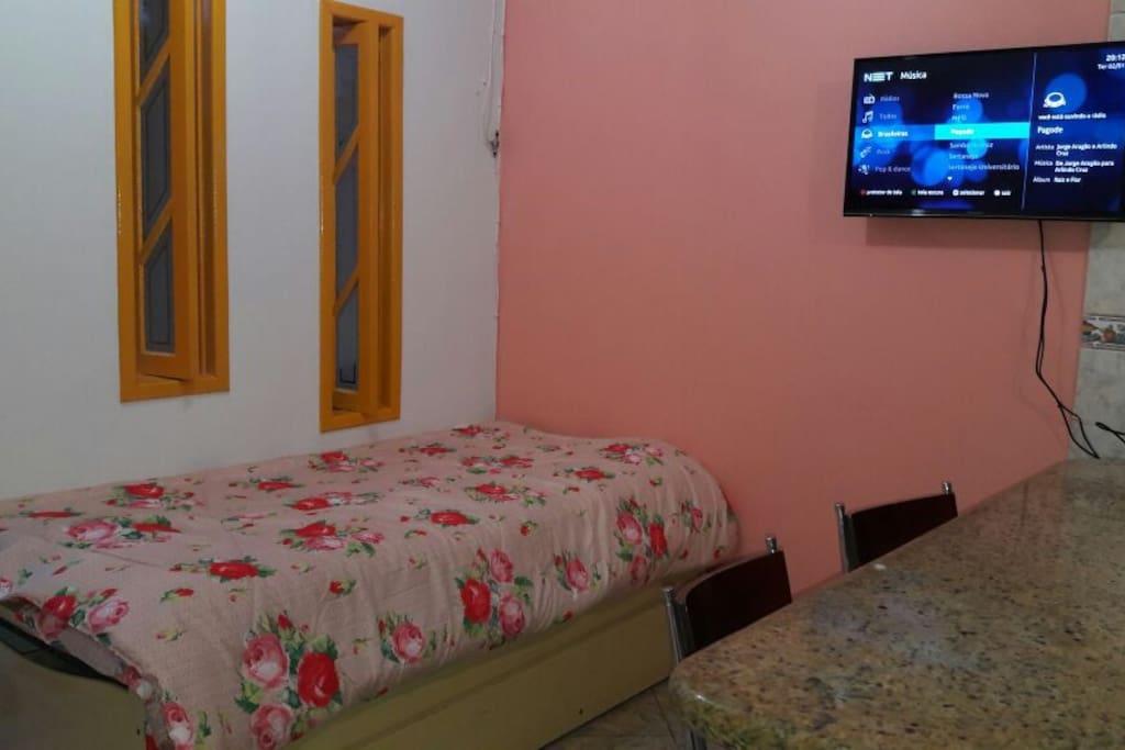 Sala e cozinha conjugada, cama de solteiro com cama gaveta anexa, TV 32', mesa bancada com 4 banquetas.