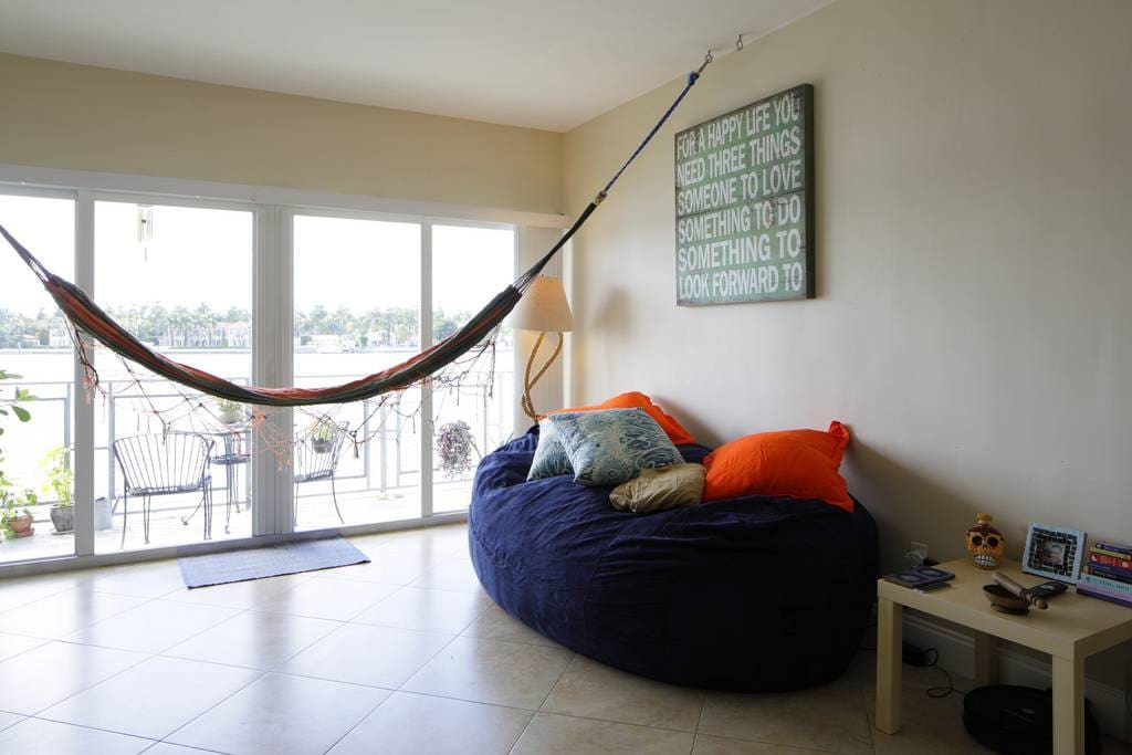 Living room has cozy 2 person bean bag sofa and hooks for two hammocks to watch movies from.