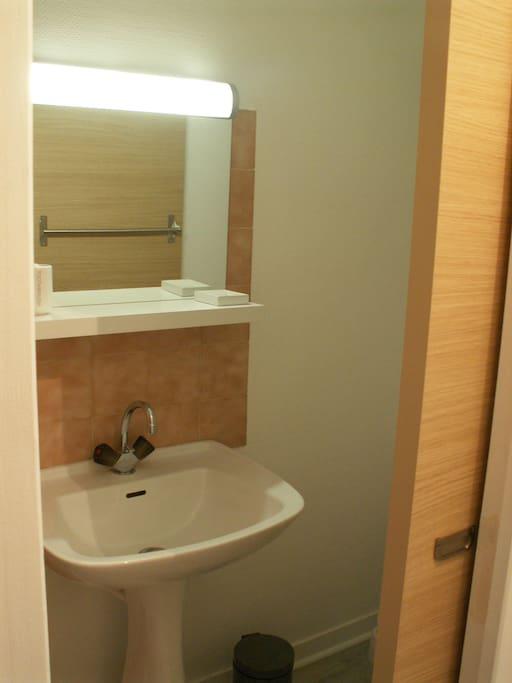 Propre, simple et porte coulissante pour un meilleur accès. La douche sur votre gauche, les wc à votre droite.