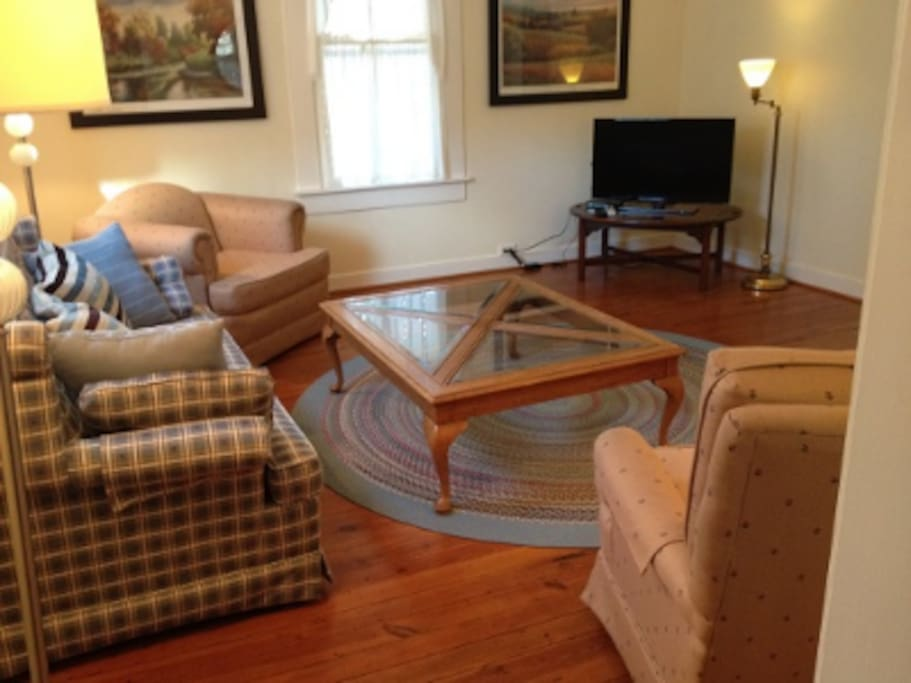 The living room of The Dogwood Suite, with sofa and TV.
