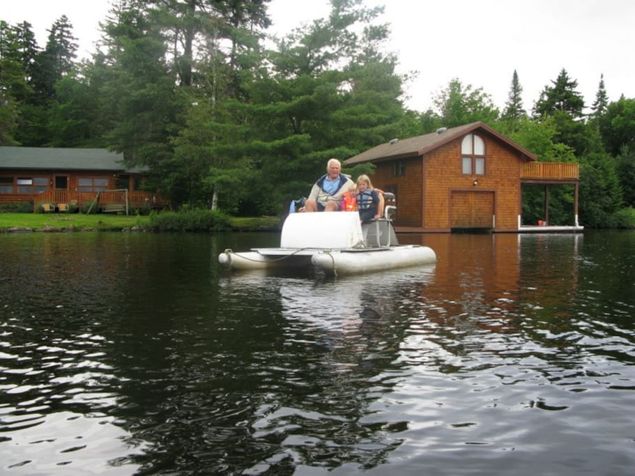 View of boathouse on right and cabin on left with pedal boat