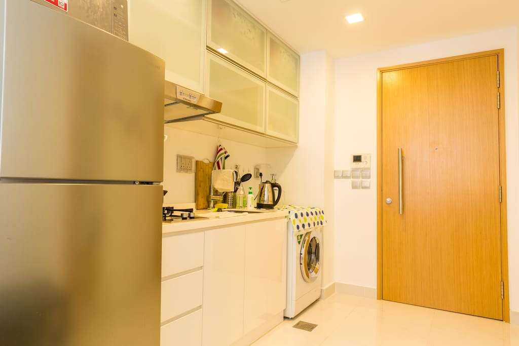 Clean kitchen area and washing machine with dryer.
