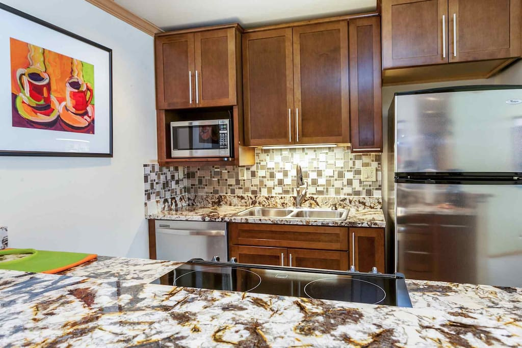 Fully equipped kitchen with stainless appliances, granite counter tops and bar seating for three.