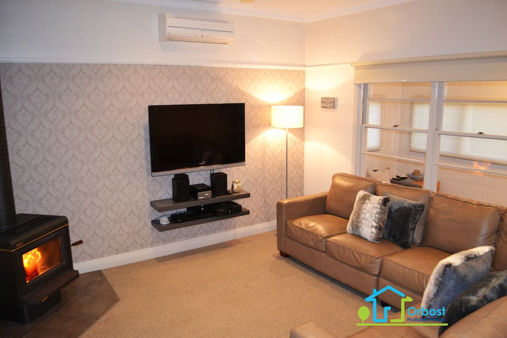 Lounge room with wood heater, split system heating/cooling