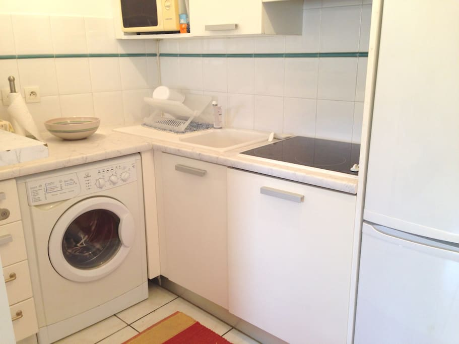 fully accessorized kitchen includes a microwave oven, washing machine, dishwasher