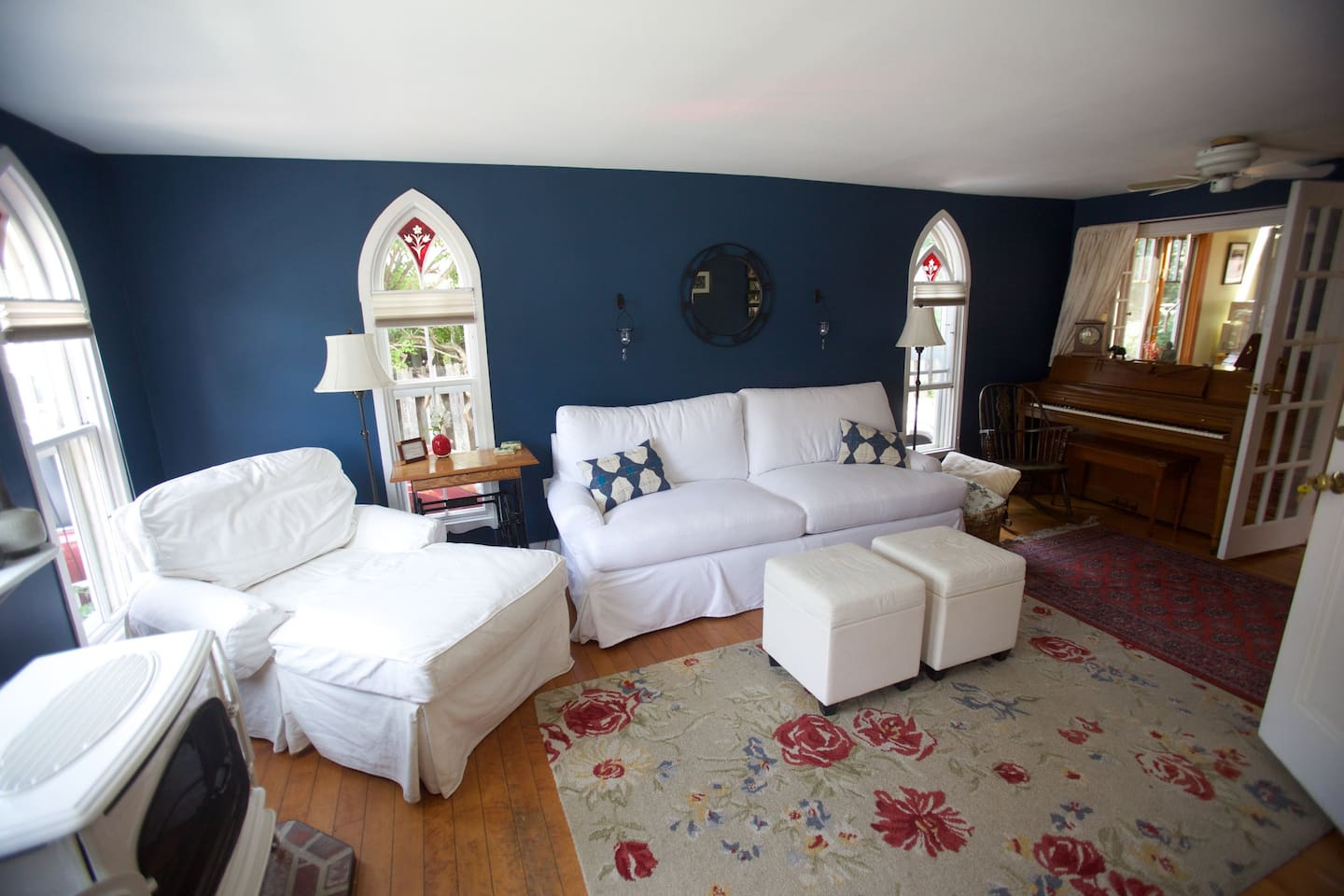 Living room with historic cathedral ruby glass windows, brand new high end sofa bed, pellet stove and piano. This living room can be closed off entirely with french windows and doors for privacy, and used as a lovely second bedroom.