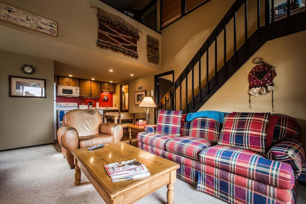 Vaulted ceilings compliment an open living room with fireplace, HDTV and comfortable furnishings.