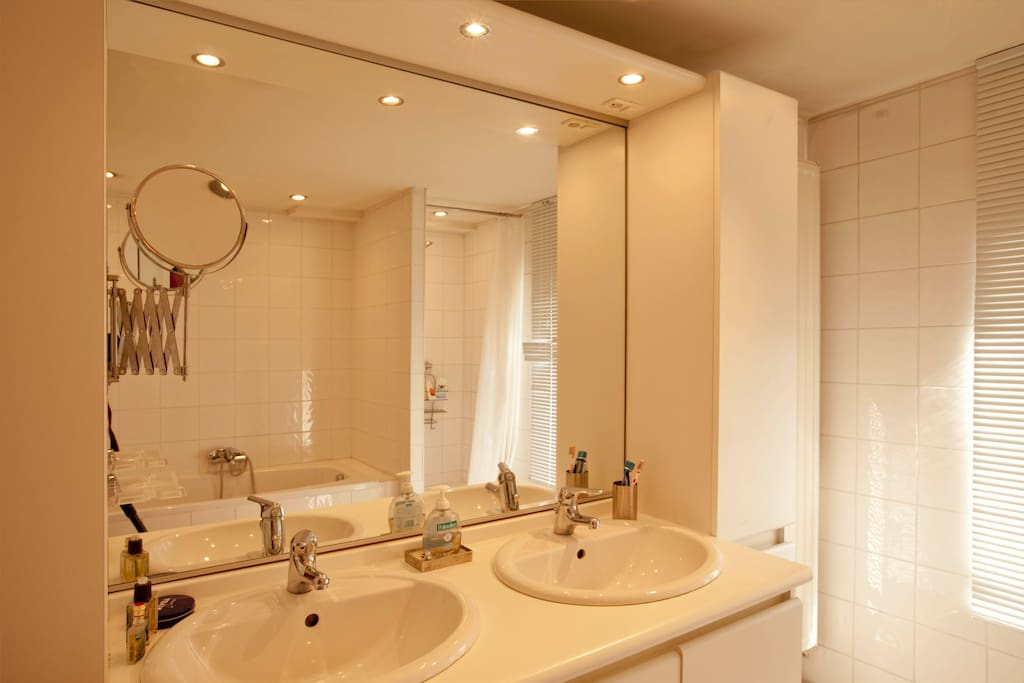 Jack and Jill sinks - mirror reflects bath tub and shower cubicle in the mirror