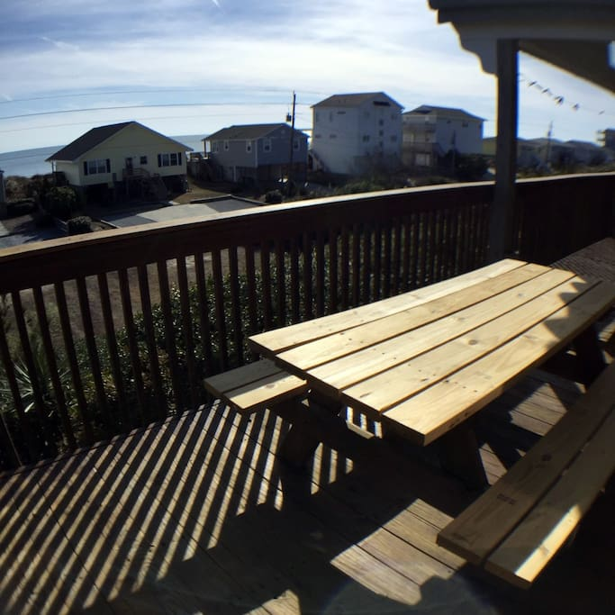 Breathtaking view of the ocean from the oceanside patio with a table and two rocking chairs.