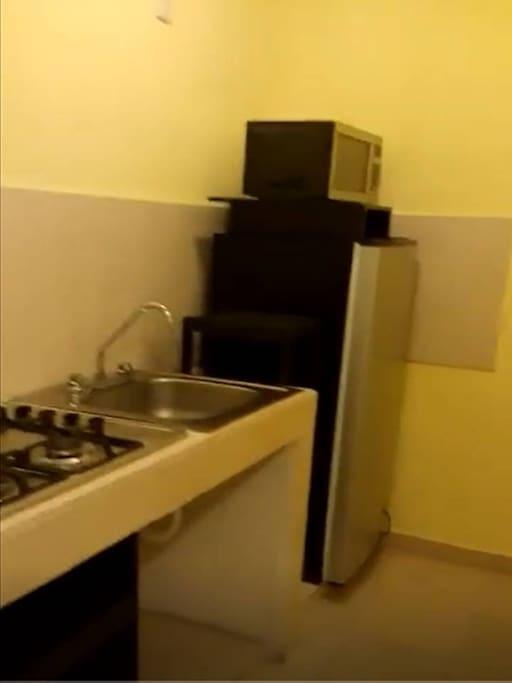 Cocina. Cuenta con una estufa de 4 quemadores con gas natural, un refrigerador de 11 pies y un microondas. Cuenta con sartenes, platos y utensilios básicos de cocina