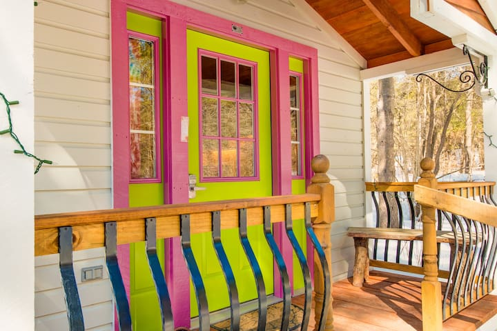 A cheerfully colored door welcomes you to the Apple Blossom Cottage.