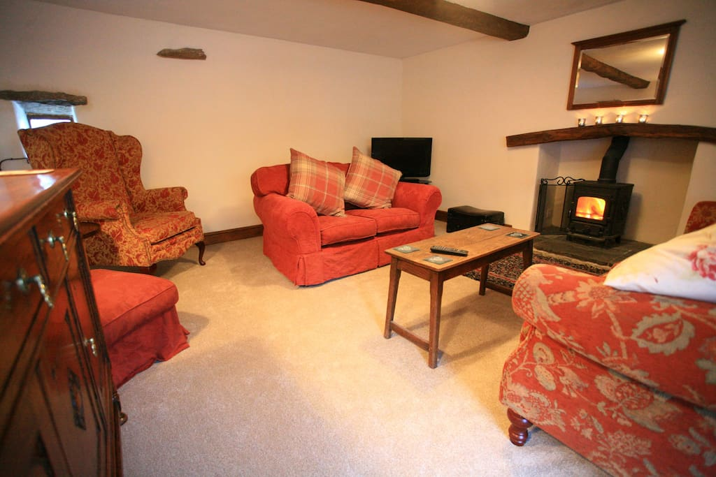 Beautifully furnished south facing living room with wood burning stove - pile of logs provided.