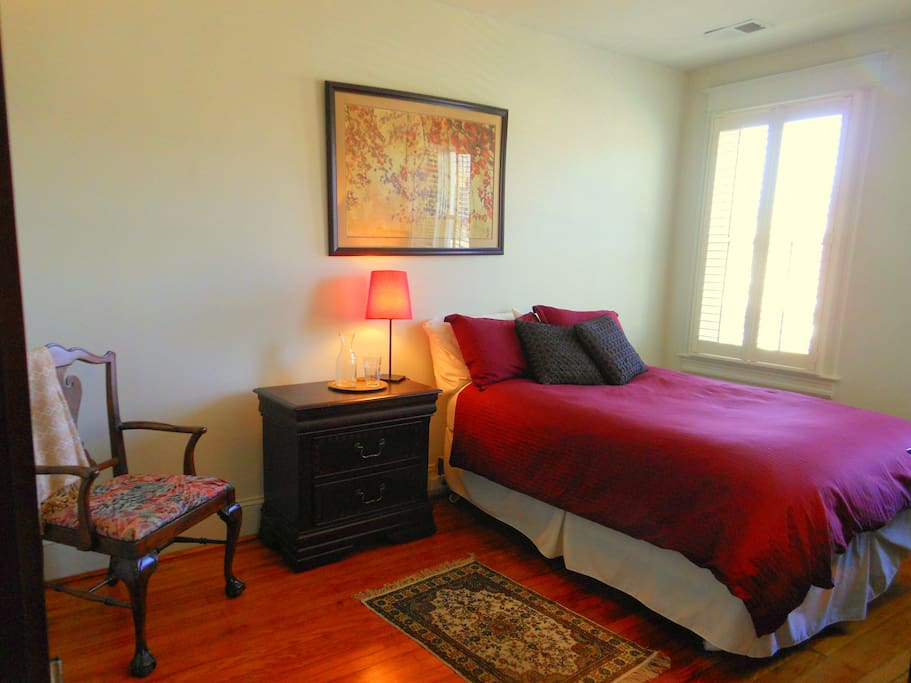 Sunny large bedroom with comfortable full-sized bed