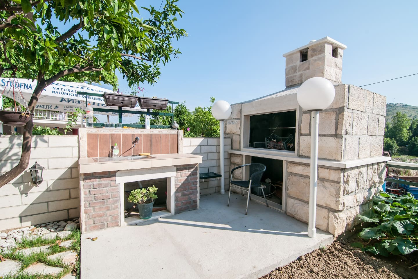 Outdoor grill with a small garden next to it is located on the ground floor