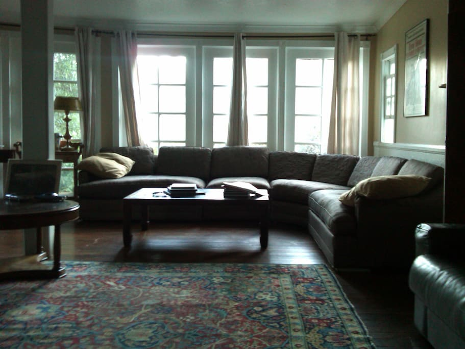 Living room with mid-century sofa, antique fixtures and floor to ceiling windows.