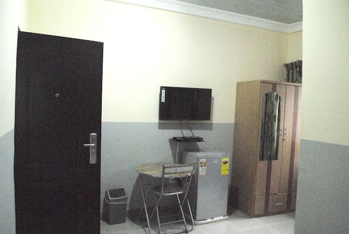 View of side of room with TV and fridge.