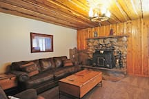 Cabin style living room with wood burning stove and flat screen TV.