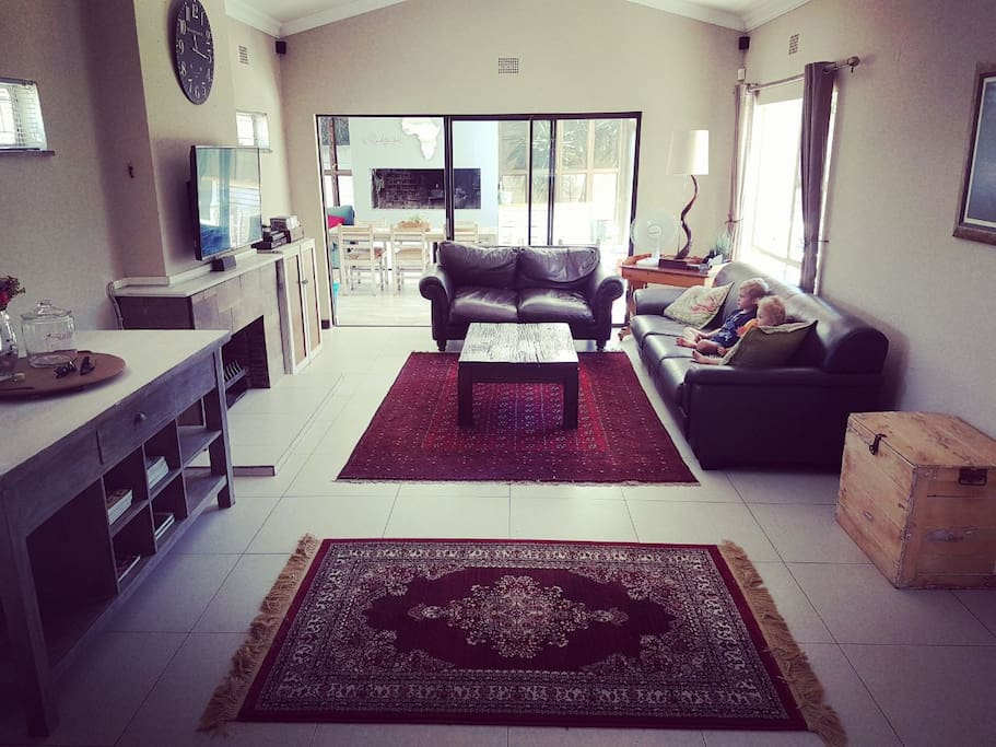 Sunny and spacious living area, leading to braairoom and outside patios.