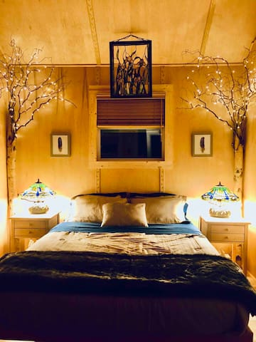 Platform bed with hybrid memory foam coil mattress. Tiffany style lamps and tree branch lights.