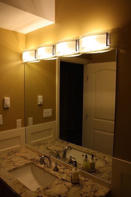 Bathroom with full shower and granite countertops.