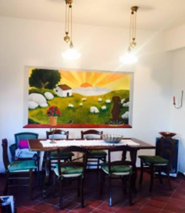 L'ampia sala da pranzo, comunicante con la cucina è impreziosita da un trompe d'oil agreste. Un ambiente molto accogliente da condividere con la famiglia e gli amici.