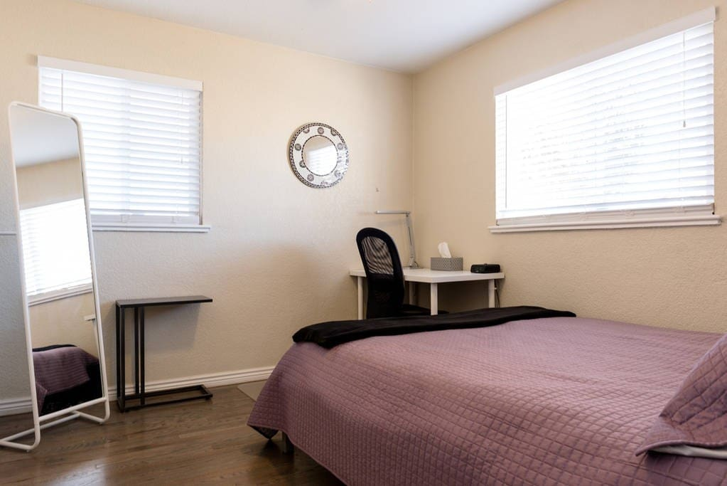 The room has a full-length mirror, small table, and a full desk with lamp and alarm clock.