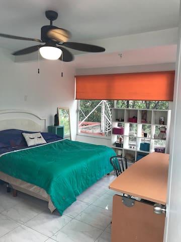Habitación amplia con escritorio y terraza.