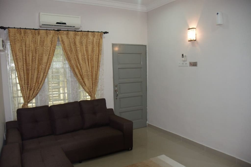 This is the living room. It is furnished with 3 seater sofa , air conditioner, and a foot massage.