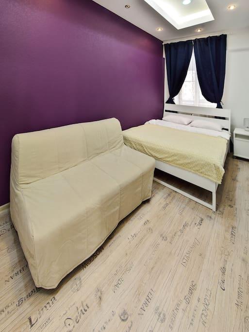 Большая кровать и диван в номере