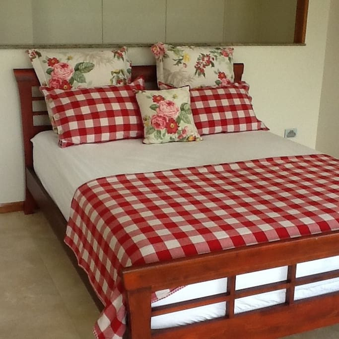 The guest queen size bed, made up with vibrant linen,