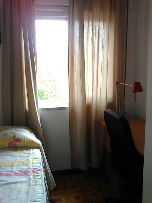 Escritorio con silla de despacho ubicado junto a la ventana con muy buena luz y ventilación.