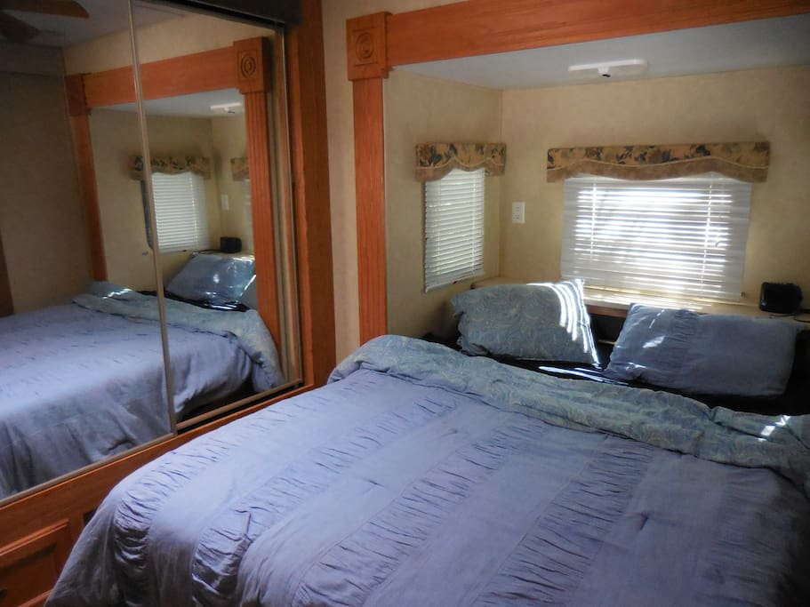 Bedroom with closets, built in drawers, doors and a queen size bed