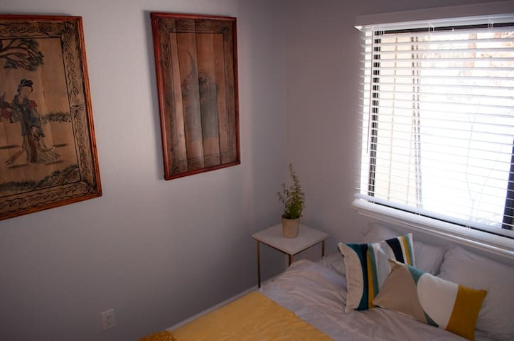 The guest room is warm and cozy with a queen bed and some Asian art