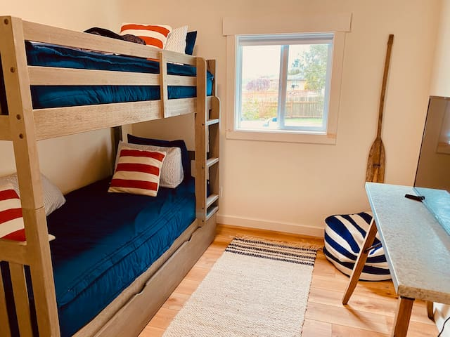 Bunk room with trundle bed and smart TV.