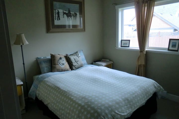Queen sized bed in cozy room with large flat screen TV and PVR.