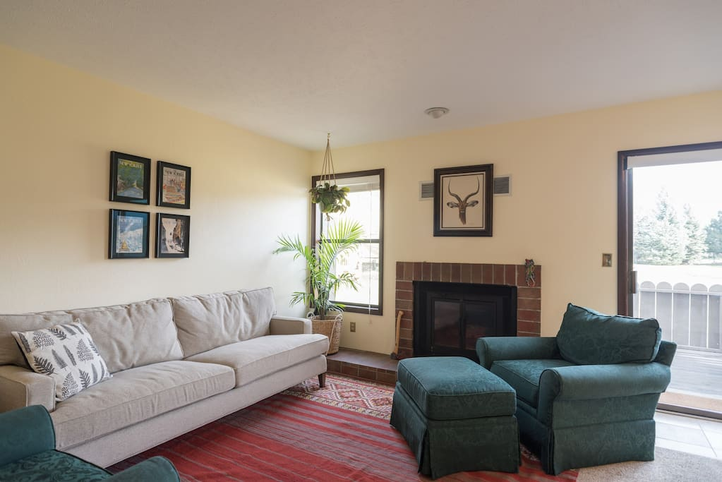 Our spacious living room has a gas fireplace and looks out over green space.