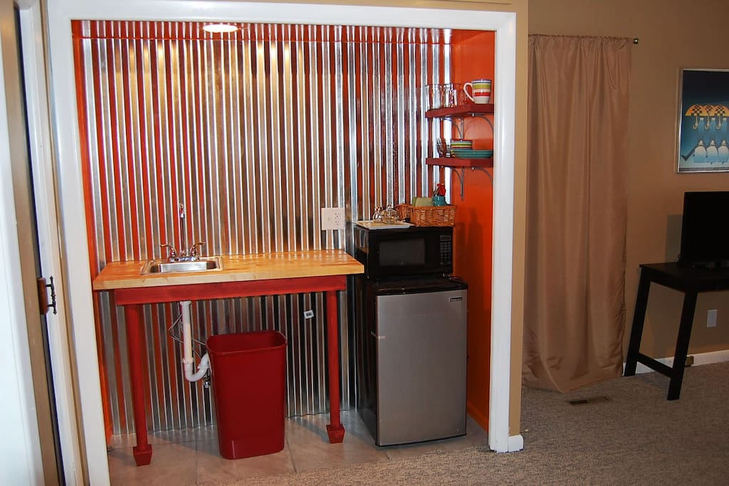 Kitchenette  with refrigerator, microwave, water kettle, dishes, utensils.