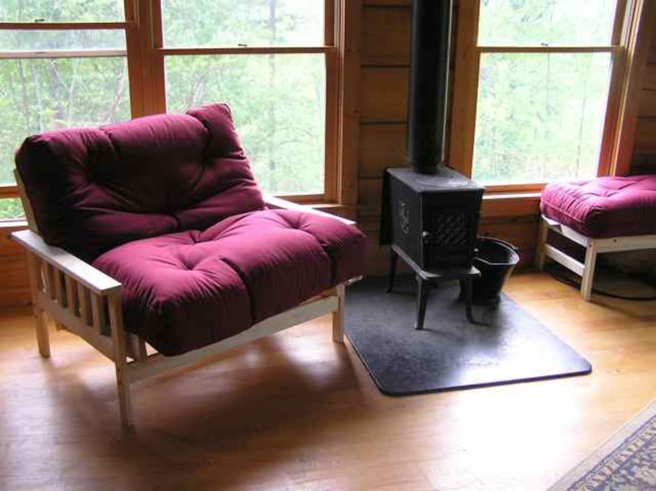 Wood stove and love seat futon in the great room - lots of light!.