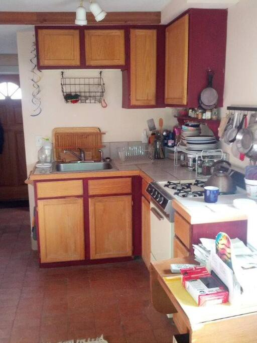 Fully equipped kitchen with stove, fridge, cabinets and utensils.