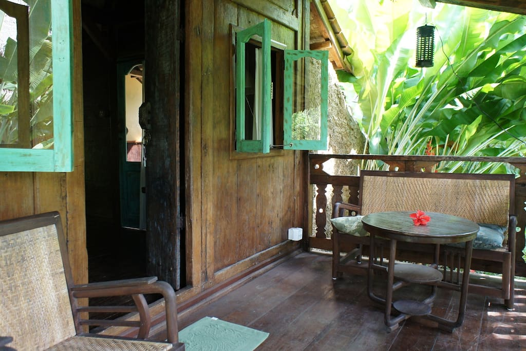 Javanese furniture on the porch, overlooking the splendid view of a small river valley and rice terrace beyond