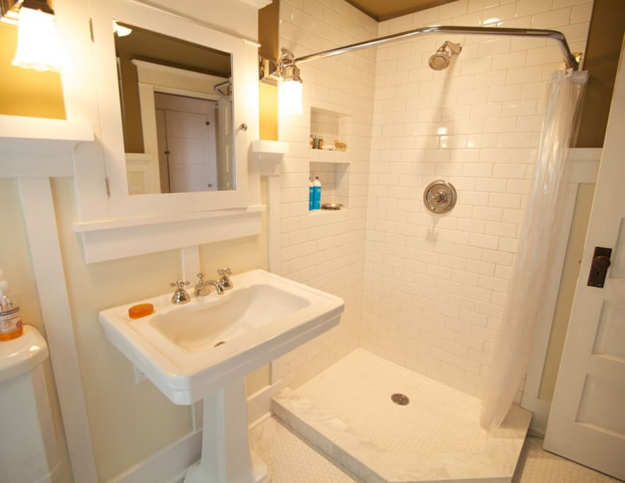 Bath with subway and marble tile shower.